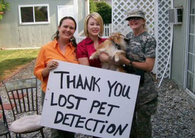 Annalisa Berns and Landa Coldiron with a dog that had gone missing in Los Angeles but recovered. Sign says Thank you!